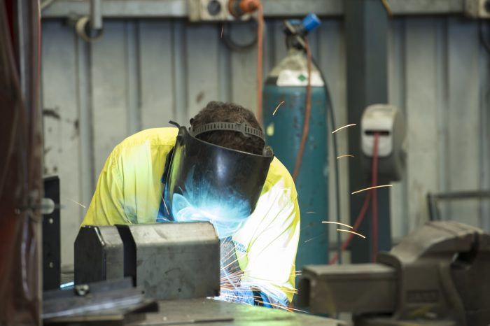 A welder fabricates equipment for the mining industry.